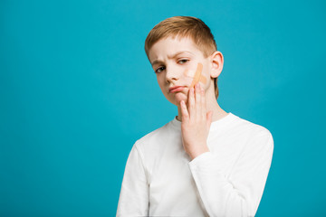 Unhappy boy with adhesive plaster on his cheek