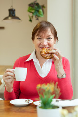 woman  with   cup of coffee and   bun.