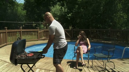 Couple sat in chairs at poolside.  Man gets up and serves up BBQ from grill. Camera on slider, wide shot.