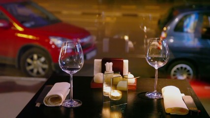 Candle burns at table with glasses and chopsticks, cars parked near road behind window