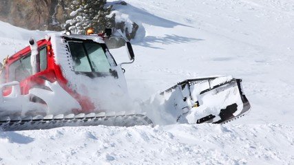 Snowplow cleans snow on mountain road in afternoon