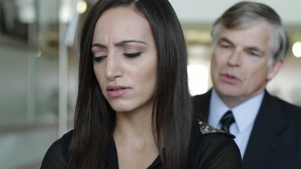 Woman is fired with regret by a male employer in a modern office building.  Employer tries to offer some comfort and sympathy.  Close up with shallow focus.  Could also be used to illustrate different kinds of relationship ending.