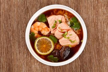 Asian soup with seafood, salmon, shrimp, lemon, mushrooms and ri