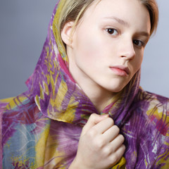 girl in a colorful scarf on a gray background