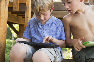 Two brothers playing on their digital tablets.