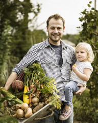 Man standing in his allotment with his daughter, smiling, holding a box full of freshly picked vegetables.