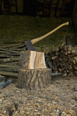 Axe stuck in a piece of wood on top of a chopping block, a pile of logs and chopped wood.
