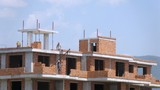 Workers erect balconies from brick in new building at top floor, time lapse poster