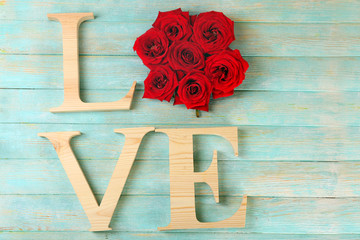 Beautiful roses with word LOVE on color wooden planks