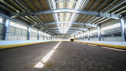 Indoor horse riding hangar with sandy covering