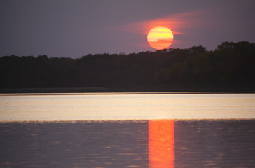 An orange setting sun casting light onto the surface of a lake.