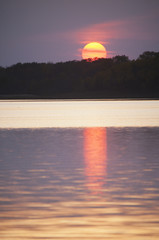 An orange sun sinking below the horizon, reflected in the water of a lake.