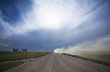 A truck raising dust as it rolls down a prairie road.