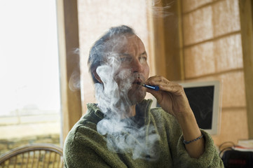 A man using an electronic cigarette, vaping.