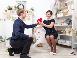 Handsome gentleman presents heart to his beautiful lady on white