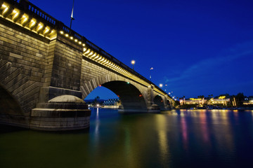 London Bridge at night, spanning the waters of Lake Havasu. Reflections in calm water.