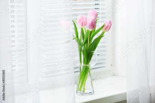 Fotobehang Tulp Beautiful pink tulips in glass vase on windowsill background