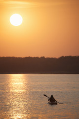 Kayaker at sunset on a calm lake.