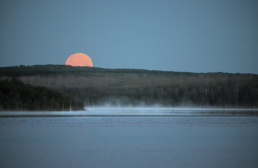 A red moon setting over a lake. Moonlight.