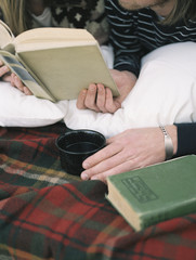 Close up of young man reading a book, holding a mug.