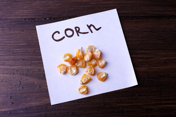 Corn seeds on piece of paper on wooden background