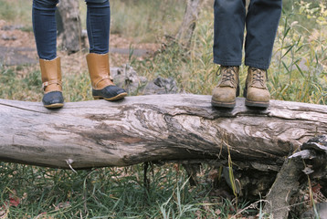 Close up of couple standing side by side on a tree trunk.