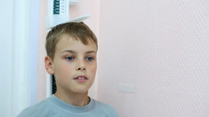 head of boy under measuring ruler in policlinic close up