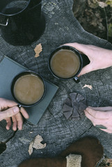 Couple having coffee in a forest, two mugs of coffee, a coffee pot and a pair of gloves on a tree trunk.