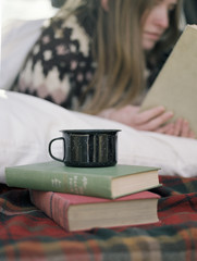 Young woman reading a book, a mug standing on two books.