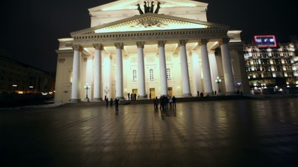 People walk by square near Bolshoi theater in Moscow at night