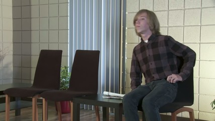 Teenager waits for an appointment, results or news.  Young woman appears and gives him paperwork to check.