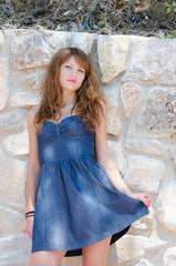 Cute fashion woman against rock wall