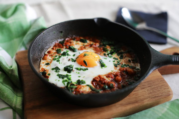 Poached egg in tomato sauce and spices, arabic shakshouka
