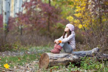 girl sitting on a log in the woods