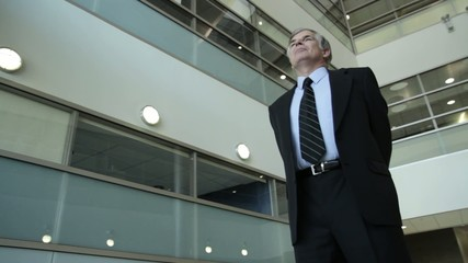 Important business man looking ahead in the atrium of a modern office building.  Three quarter shot from low angle with camera mounted on dolly.