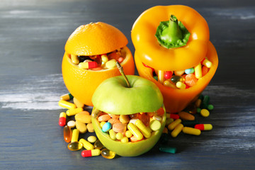 Apple, orange, paprika and colorful pills,