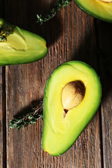 Sliced avocado with herb on wooden background