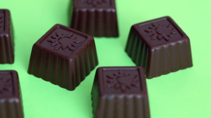 Six chocolate candies at green background, closeup view in motion