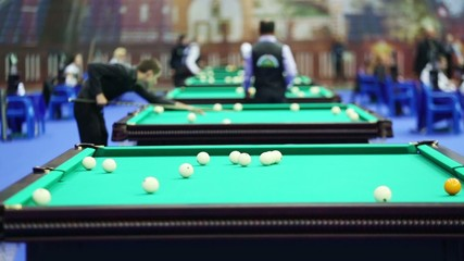 Competitors play billiards at Tournament. Focus on balls