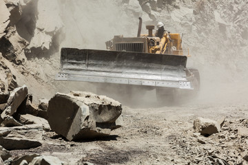Bulldozer cleaning landslide on road in Himalayas