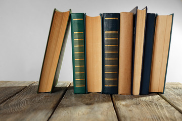Old books on wooden table on gray background