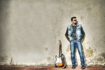 man and guitar leaning on the wall