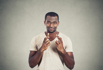 hopeful man crossing fingers isolated grey wall background