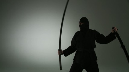 Profile view of a masked ninja unsheathing a massive two-handed katana (Japanese sword).