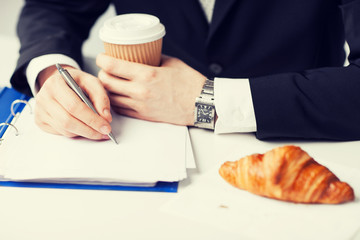 businessman with coffee writing something