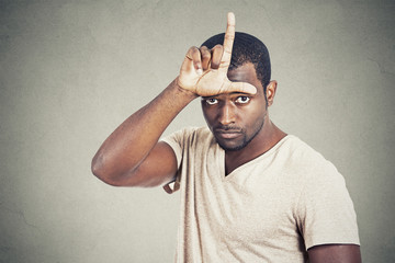 man showing loser sign on forehead looking at you