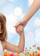 close up of woman and little girl holding hands