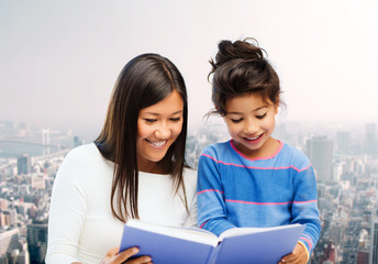 happy mother and little daughter reading book