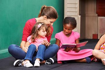 Afrikanisches Mädches liest Buch im Kindergarten