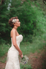 Beautiful young bride with a bouquet standing in profile